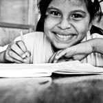 black and white close-up photo of a young girl's happy face as she writes in her journal
