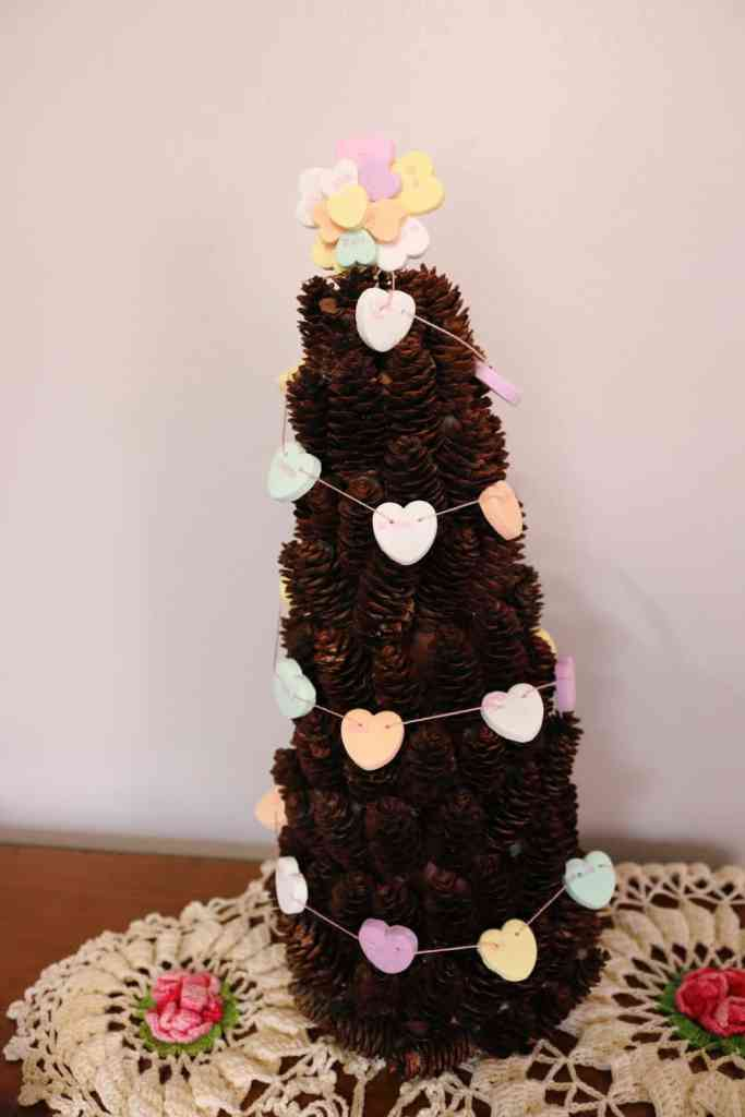 Miniature pine cone tree with conversation heart garland and topper https://www.b4andafters.com/conversation-heart-garland