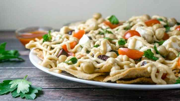These Mediterranean Nachos are a must-try! All the delicious flavors of the Mediterranean in a delicious platter with heart-healthy chickpeas, feta cheese, fresh veggies and herbs, all topped with a yummy hummus sauce. From http://www.babaganosh.org