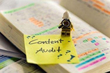Gelbes Post-It auf einem farbigen Notizbuch mit der Aufschrift Content-Audit