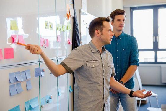 Scrum im Content-Marketing: Scrum-Master Michael Diel moderiert vor dem Scrum-Board das tägliche Daily Scrum.