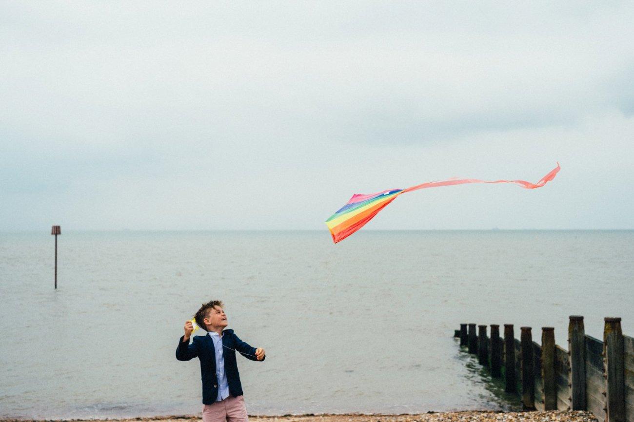 Boy flying kite Kent seaside wedding