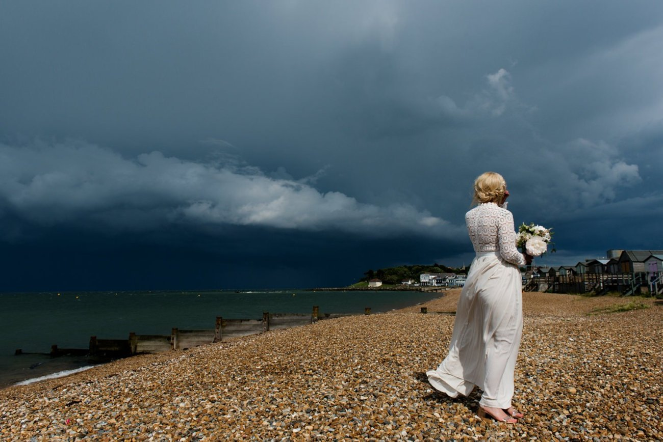 Bride on beach with storm clouds