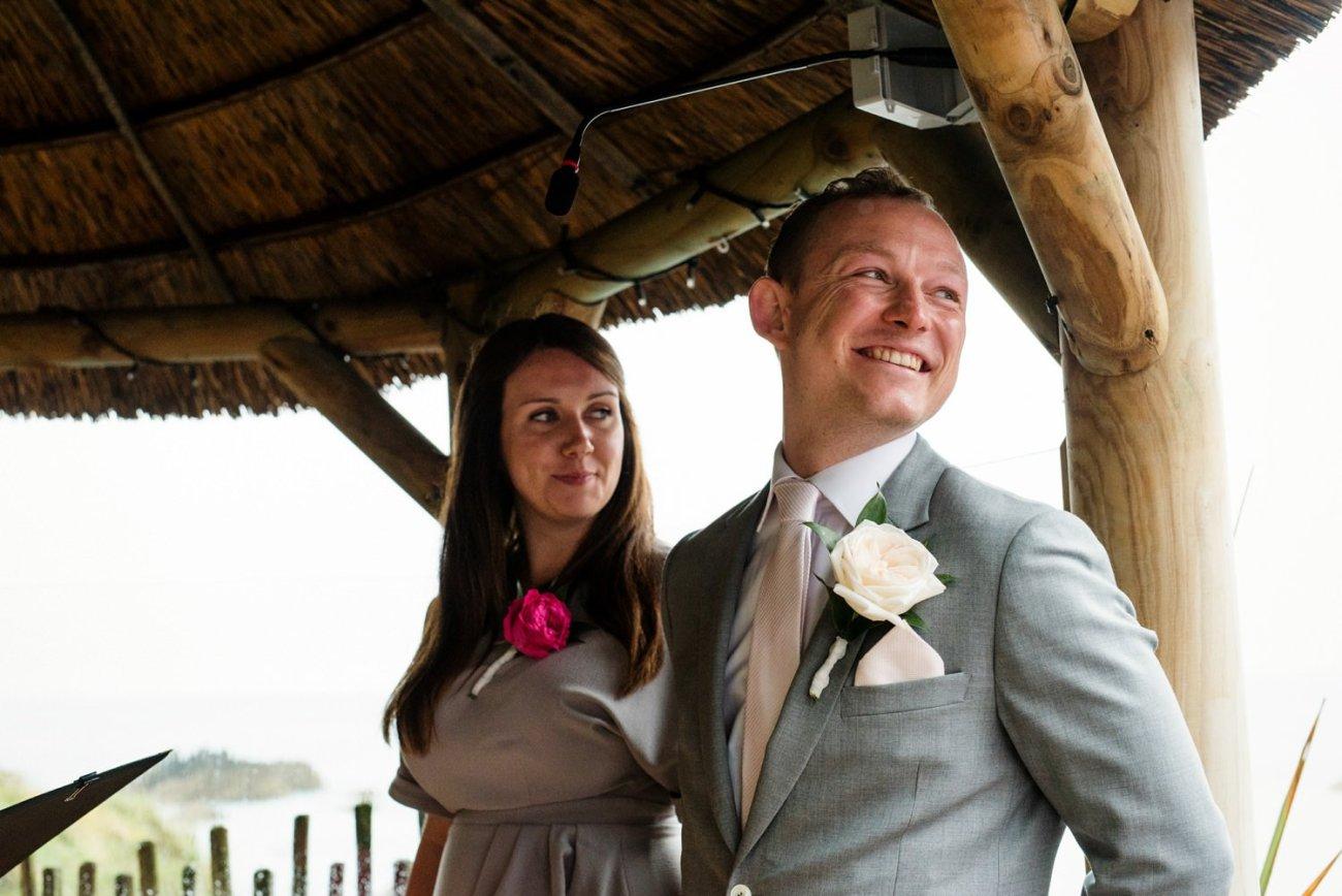 Smiling Paul Smith Groom Devon beach wedding ceremony