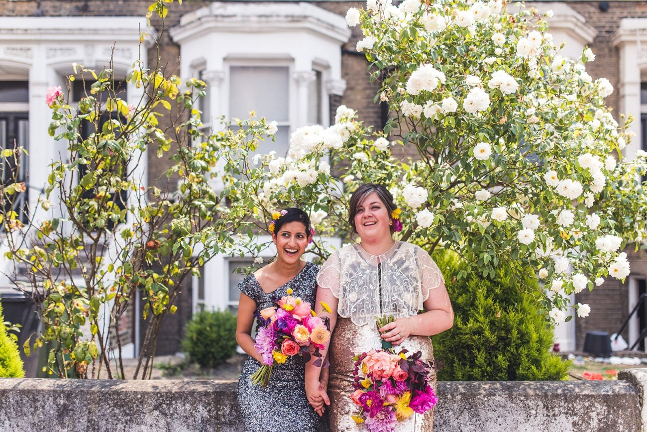 Two brides sitting on a London wall in sequinned dresses