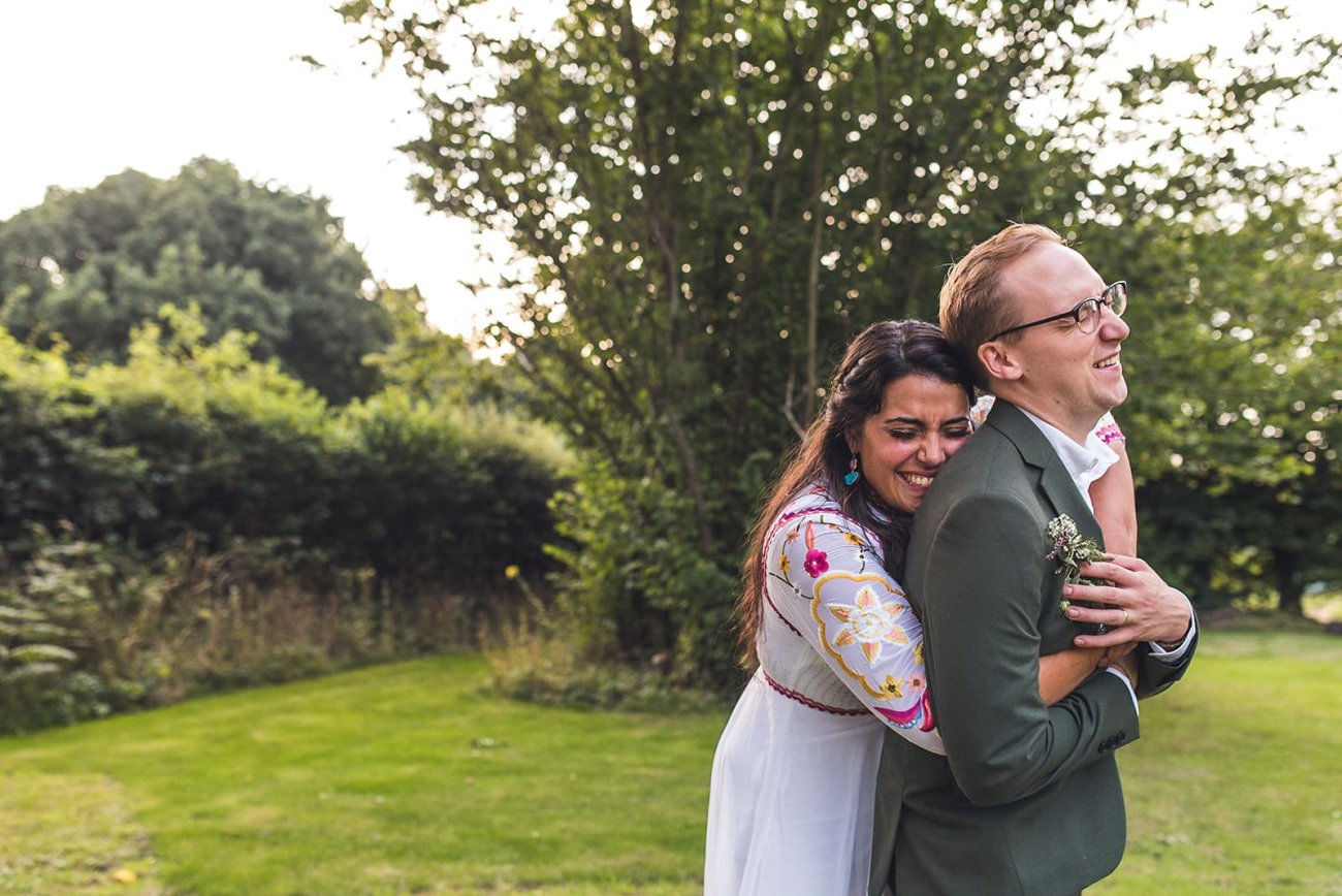 Bride in colourful wedding dress and groom in tweed suit at the Keeper and the Dell Norfolk