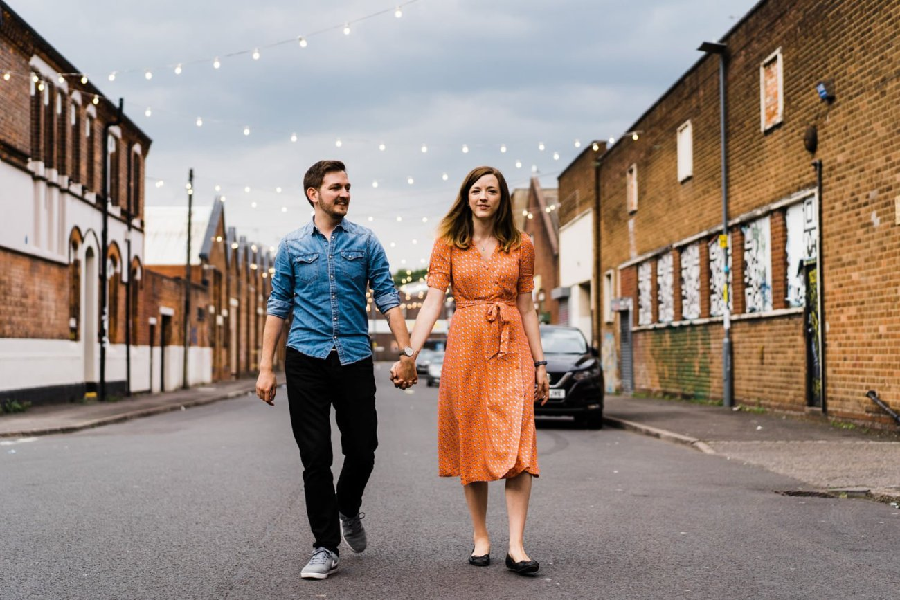 Couple walking through Digbeth with girl in orange dress and boy in denim shirt