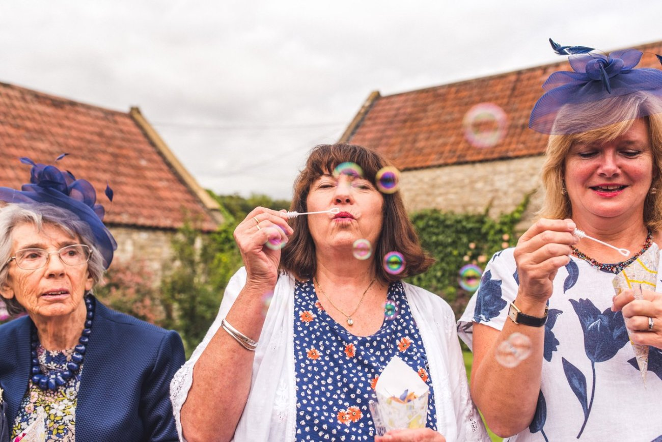 Guests blowing bubbles at Priston Mill wedding