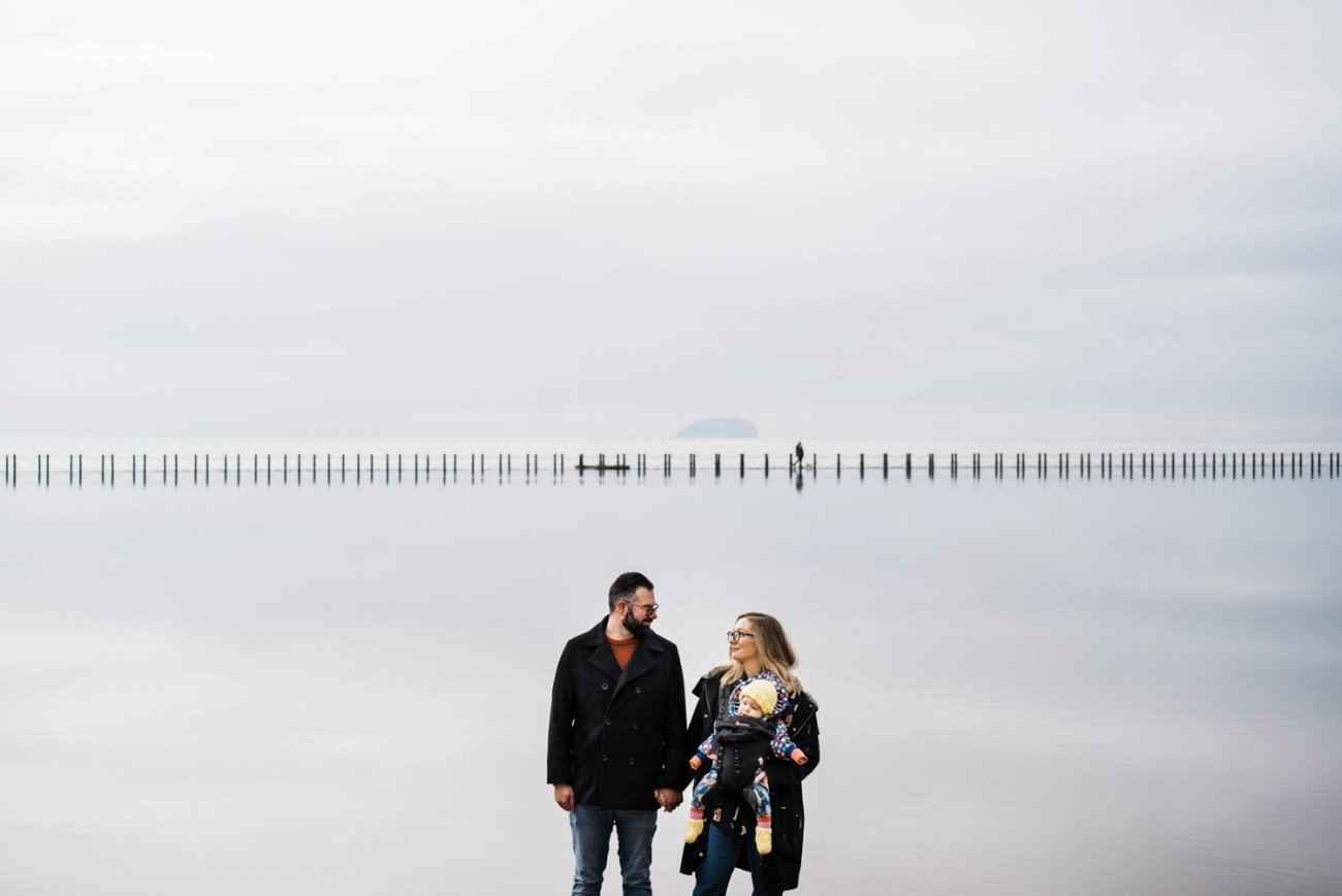 A couple and their baby standing in front of still water in Weston-super-Mare