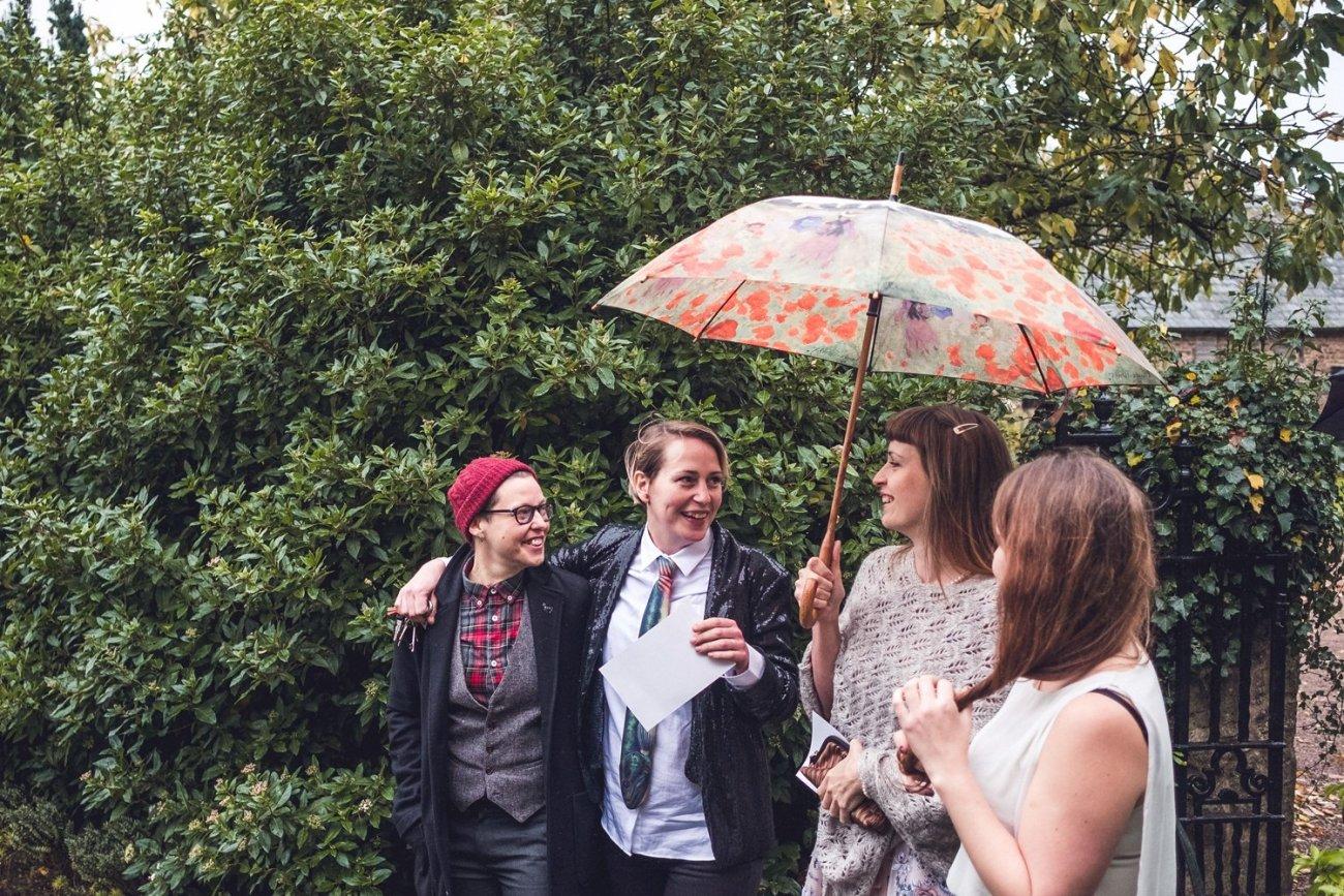 Wedding guests sheltering under umbrella Bride and groom Rainy-Dewsel-Court-Wedding