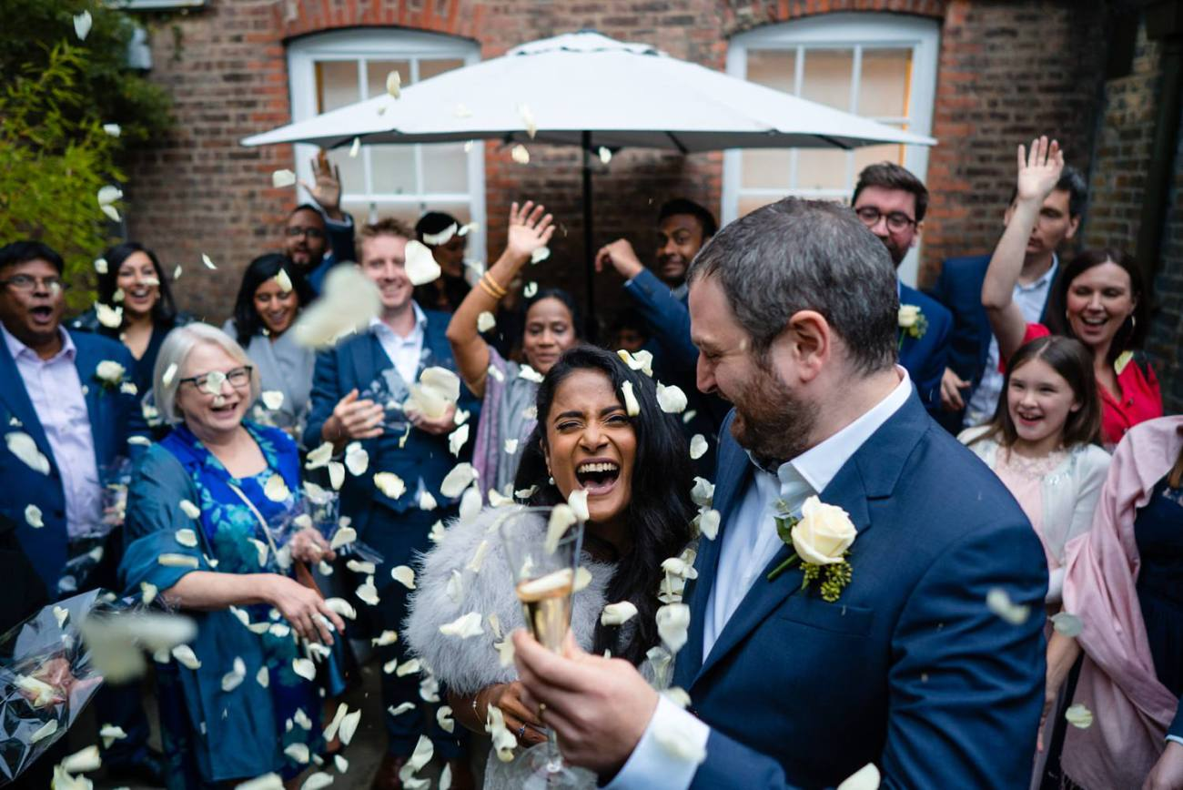 Bride laughing as confetti showers down on her Burgh House