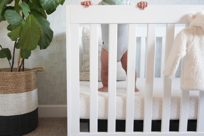 Cropped image of baby standing up inside his crib.