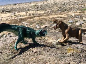 two dinosaurs fighting on a rock