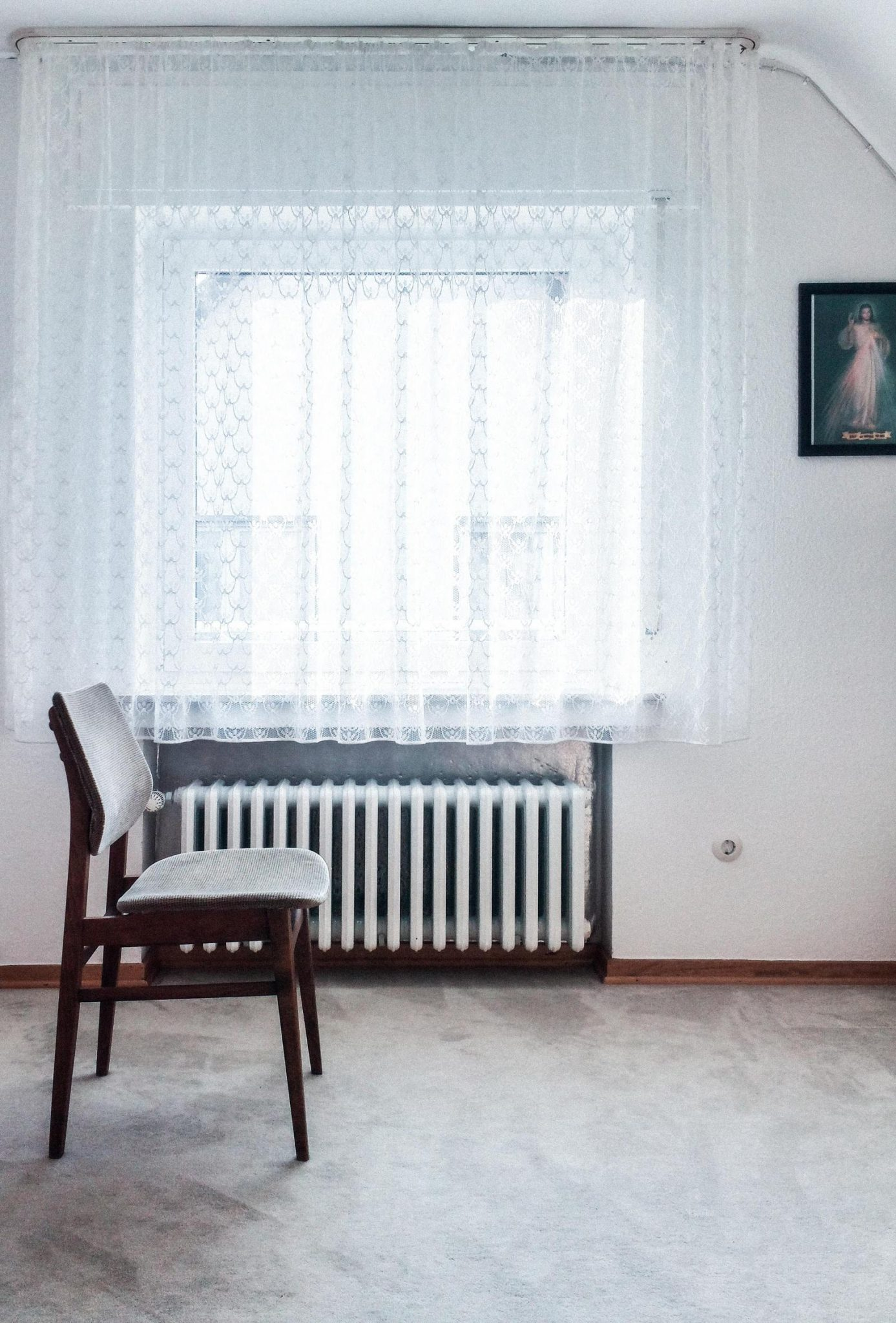 oil radiator in room with chair in foreground