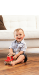boy playing with toy truck in the living room, sitting and smiling for the camera