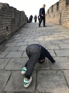 Toddler doing a sun salutation on the Great Wall.