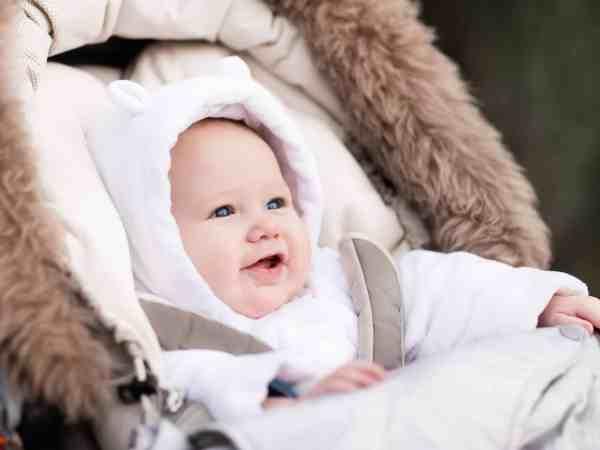 62520453 – happy laughing baby enjoying a walk in winter park sitting in a warm stroller with sheepskin hood