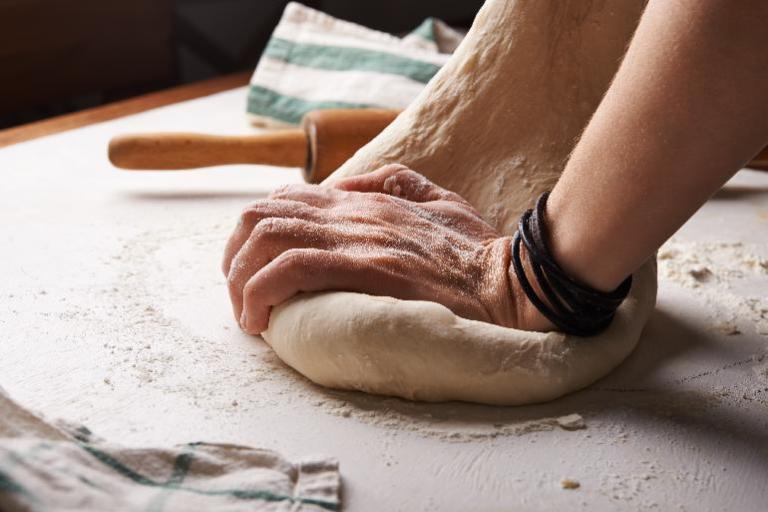 Hände kneten einen Teig