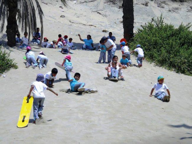 Schoolkids sandboarding in Huacachina