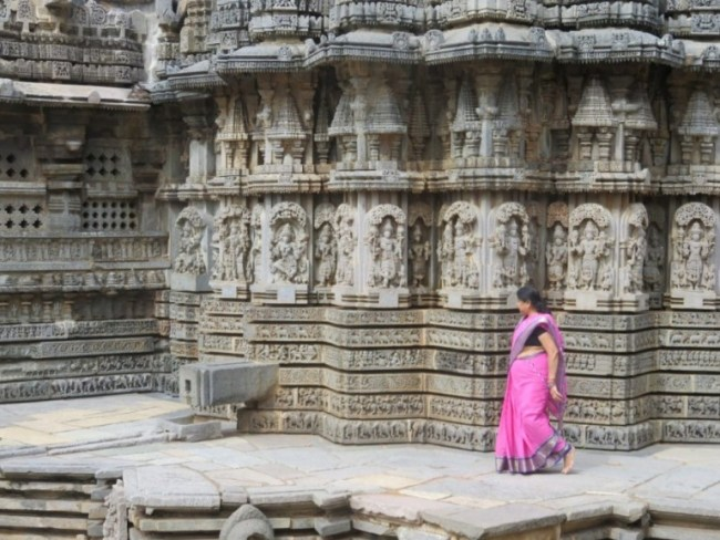 women with pink saree watching at the carved details at the temple in somnathpur