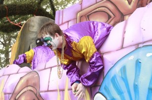 Mardi Gras float purple and gold throwing beads