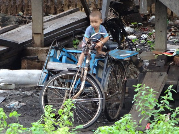 Local youngster getting onto a big bike (Myanmar, 2016).