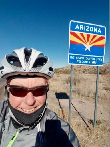 man wearing bike helmet by Arizona welcome sign