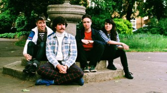 Promo image of The Spook School band sitting in front of a fountain