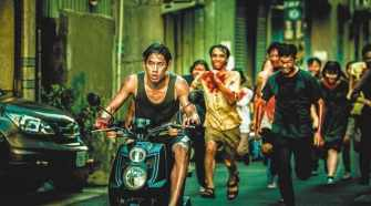 Jim on a moped being chased by the infected