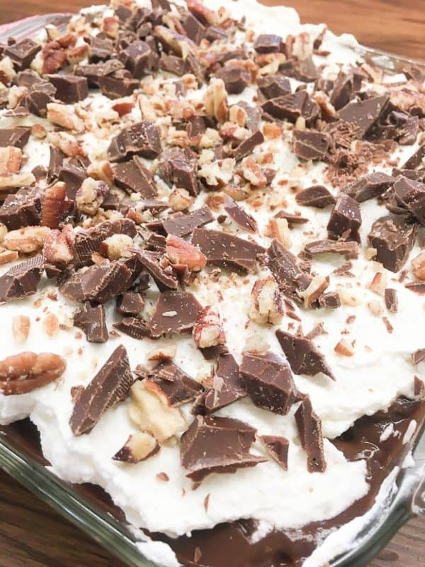 Chocolate layer dessert with a graham cracker crust, homemade whipped cream, chocolate pudding, and cream cheese is a delicious recipe. The easy recipe is the perfect dish for a party, the holidays, or for dessert at home.