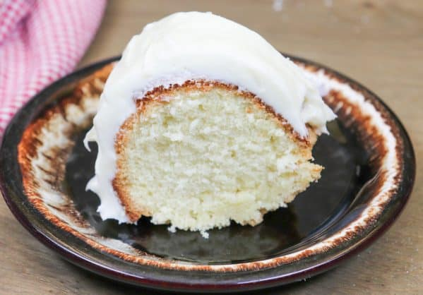 Picture of pound cake with cream cheese frosting on a plate.