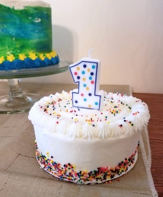 Picture of white birthday cake with green and blue birthday cake in the background.