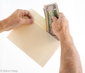 Caucasian ethnicity hands putting fifty dollar bills in envelope
