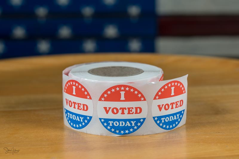 Roll of I Voted Today paper stickers on table with US Flag in ba