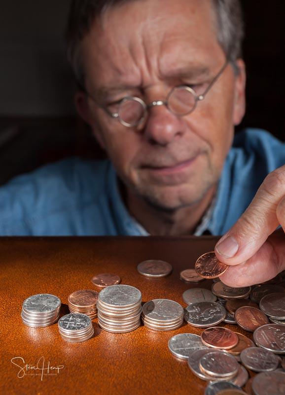 Senior man counting cash into piles