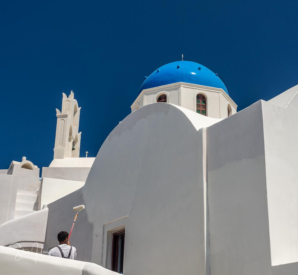 Man painting the white walls in Santorini