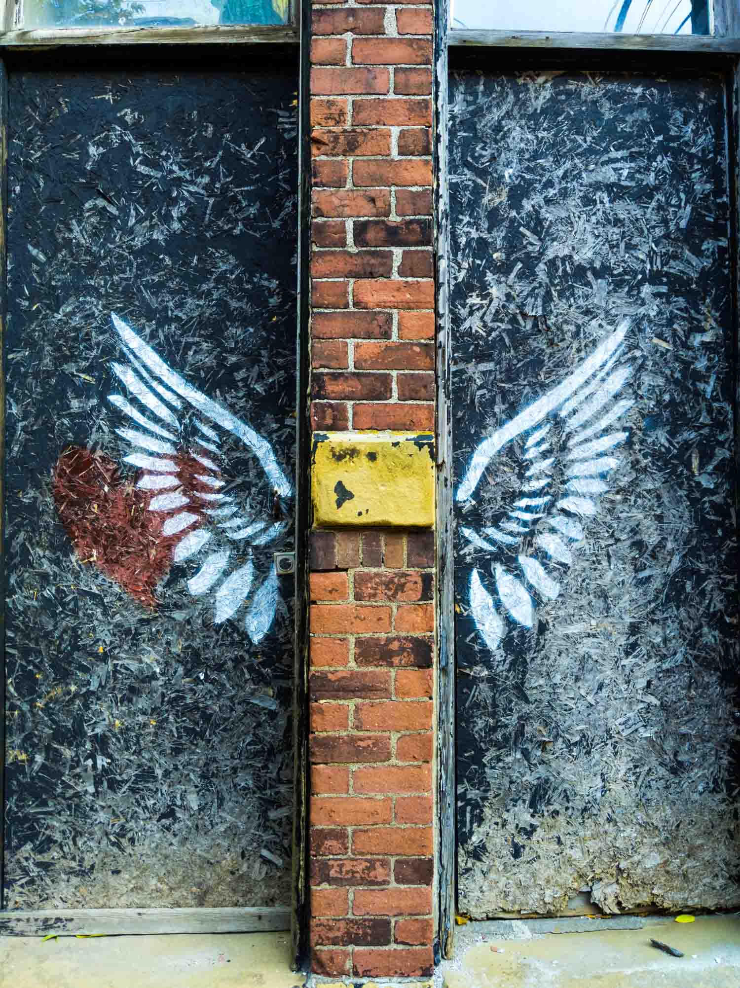 Stenciled wings on a building in restoration.