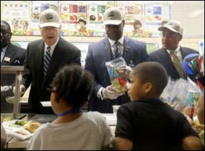US Secretary of Agriculture Tom Vilsack, Richmond schools Superintendent Dana T. Bedden, and US Rep. Bobby Scott work in the lunch line at Woodville Elementary on March 9, 2015. Photo credit: Richmond Times-Dispatch.