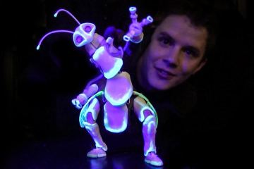 He used plastic and other materials, as well as neon to give the light effects upon darkness and created an incredible Bug puppet that glows in dark.