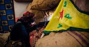 Photo from Kobani, YPJ female fighter with YPG flag