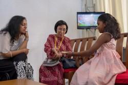 Une jeune fille présente une collection d'écrits sacrés qu'elle a rassemblés dans un livret. Datuk Lok Yim Pheng (au centre), commissaire de la Commission des droits de l'homme de Malaisie, et Omna Sreeni-Ong (gauche), membre de la communauté bahá'íe, écoutent attentivement.