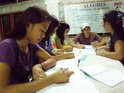 Un petit groupe de jeunes aux Philippines étudie et échange sur la documentation fournie pour le séminaire.