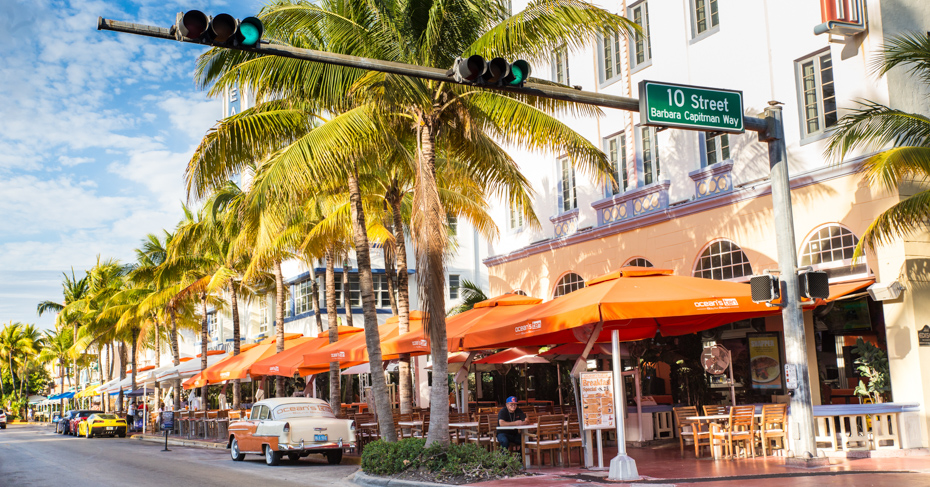 Best things to do in Miami Attractions - Ocean Drive; Miami Beach, Florida, USA - April 24, 2016: View along the famous vacation and tourist location on Ocean Drive in the Art Deco district of South Beach, Miami on a sunny day with cars, palm trees and people visible.