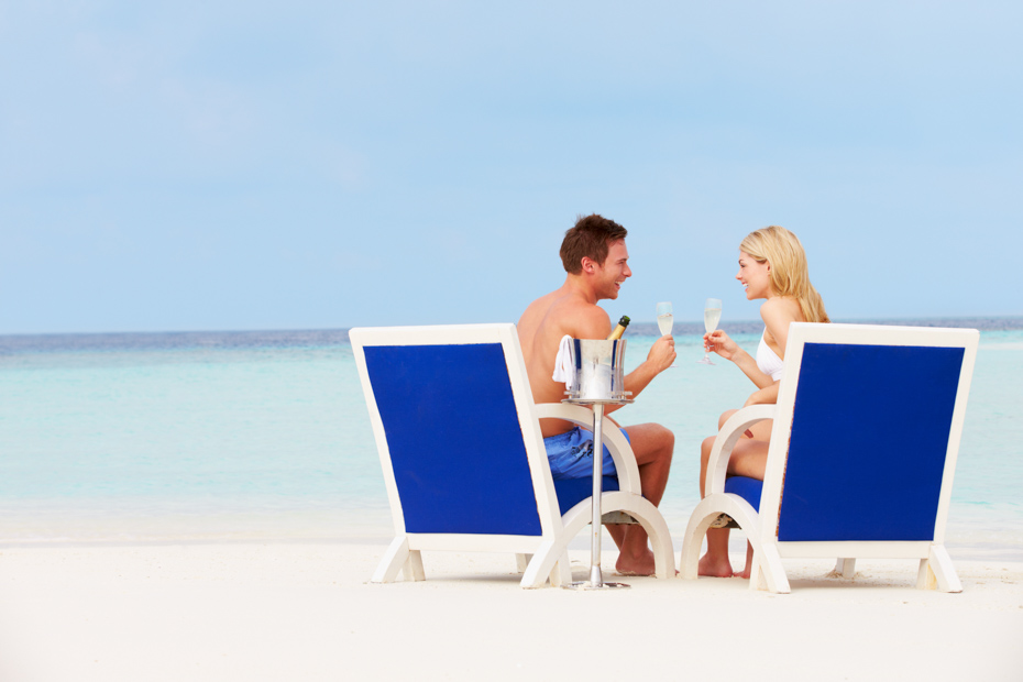 Couple On Beach Relaxing In Chairs And Drinking Champagne Looking At Each Other. Best bahamas resorts, exuma bahamas hotels, best hotels in bahamas