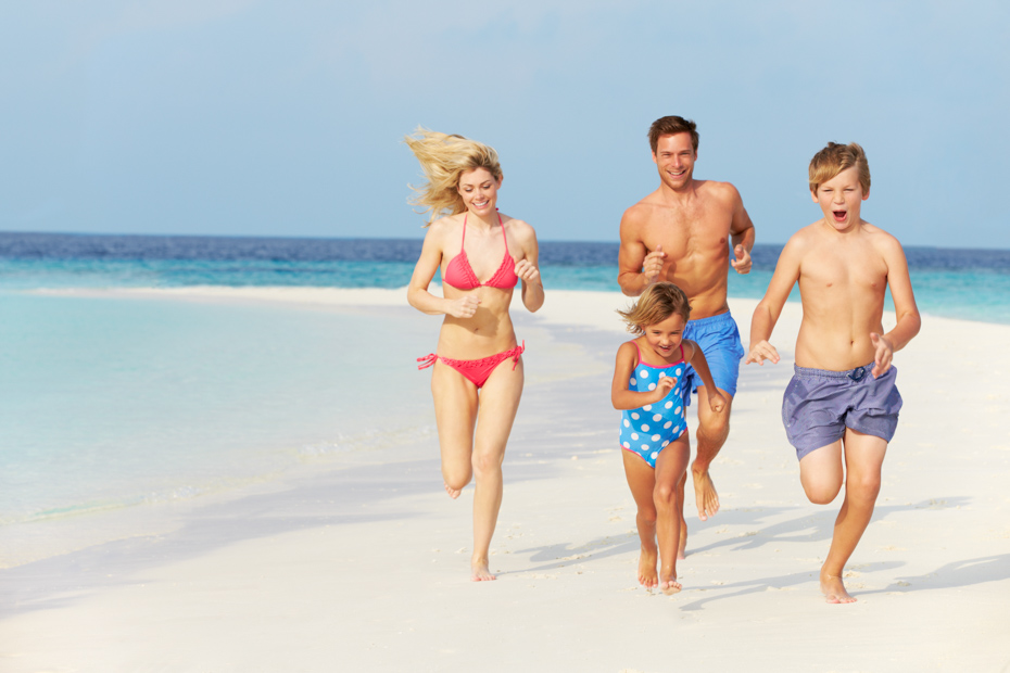 The Exuma Cays are a family-oriented Bahamas vacation. Family running on beach on day trips from Nassau to Exuma Pig Beach Bahamas.