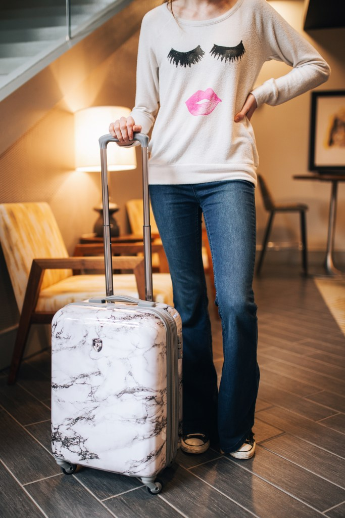 Standing with my marble Heys suitcase all prepped and ready to travel after organizing with Calpak packing cubes.