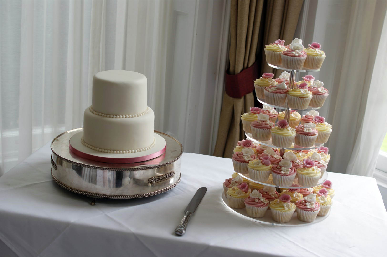 White Floral Wedding Cake With Cupcakes
