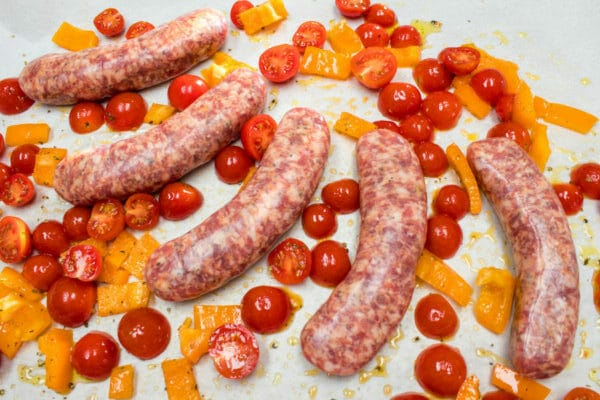 Italian sausages being prepared for baking, with cherry tomatoes and bell peppers.