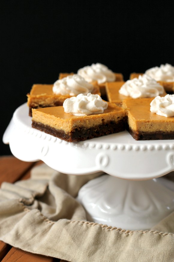 These Gingersnap Pumpkin Cheesecake Bars have a crunchy gingersnap cookie crust topped with a luscious, smooth pumpkin cheesecake filling.