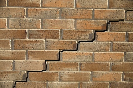Close up view of a brick wall with stair-step cracking pattern.